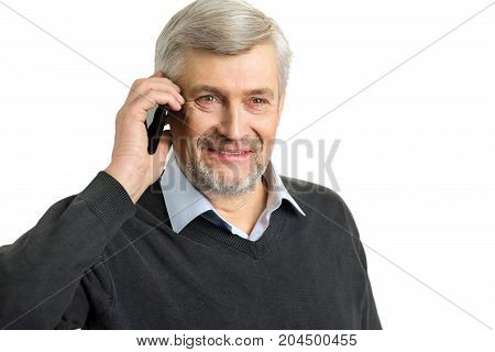 Portrait of mature man with phone. Close up of smiling elderly man speaking on mobile phone on white background.