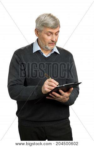 Confident senior supervisor writing on clipboard. Handsome mature man writing something using clipboard.