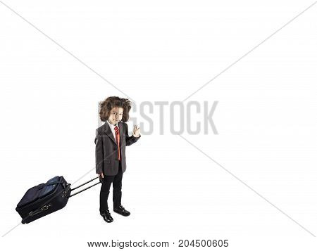 Little curly-haired boy holds a suitcase on wheels. Bussinesman in a bussines suit with baggage. White background.