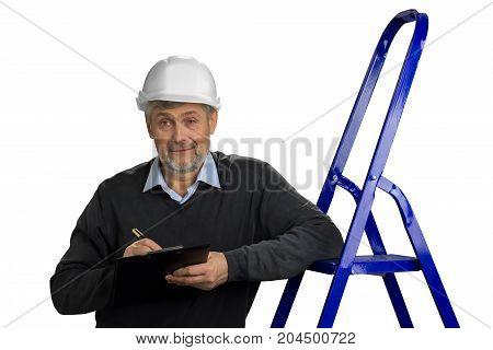 Mature engineer leaning on ladder. Senior builder supervisor with clipboard, ladder on white background.