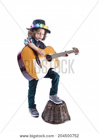 Cute Little Boy In Black Cowboy Hat Learns To Play The Guitar.the Boy Sings To The Guitar. Boy Puts
