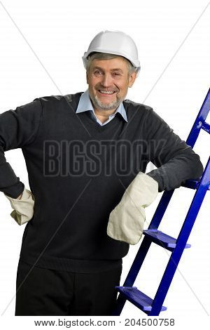 Smiling senior engineer near ladder. Mature foreman in hard hat holds hand on belt and leaning on ladder.