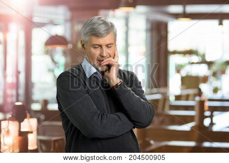 Portrait of deeply thoughtful mature man. Seriously thinking elderly man on blurred background.