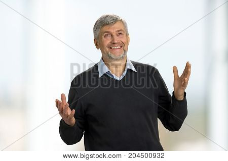 Excited mature man on white background. Mature man raising his hands, looking upwards and smiling with excitement.