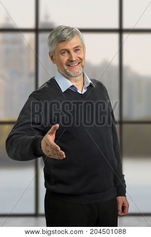 Handsome mature man with greeting gesture. Mature man give a hand to somebody on office window background.