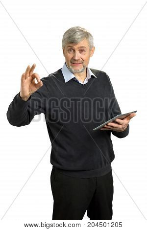 Handsome mature man showing Ok sign. Cheerful senior man in formal wear gesturing OK sign with fingers and holding computer tablet on white background.