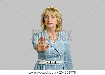 Mature woman making gesture stop. Confident mature businesswoman gesturing stop sign while standing isolated on grey background.