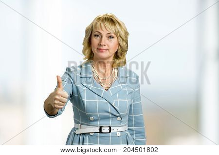 Elegant mature woman raised thumb up. Confident white-skin woman raised her thumb up. Gesture everything is okay.