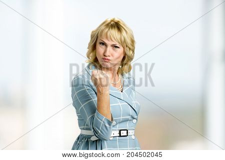 Angry mature woman showing fist. Upset midldle aged businesswoman putting up fist warning someone.