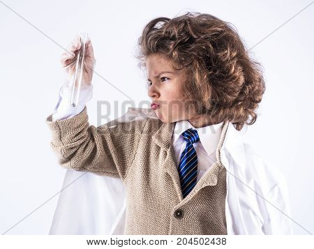 A ilittle curly-haired boy in a medical gown holds a test tube with one hand . White background.