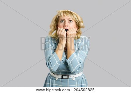 Shocked and stunned mature woman. Portrait of middle aged woman looking surprised, vulnerable, frustrated on grey background.