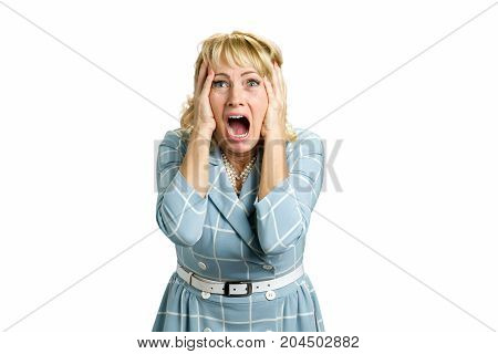 Portrait of screaming desperate woman. Mature woman yelling frustrated screaming out loud and holding her head. Stressed and shocked white-skin blonde businesswoman screaming with desperate.