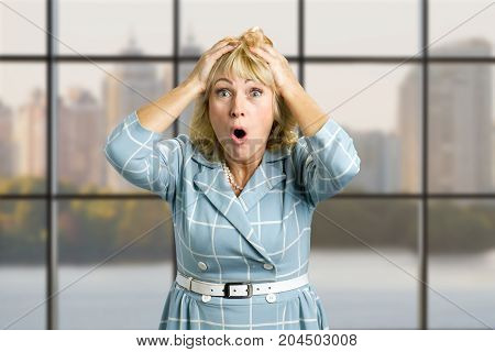 Portrait of surprised mature woman. Close up portrait of woman looking surprised in full disbelief with hands on hand and open mouth on office window background.