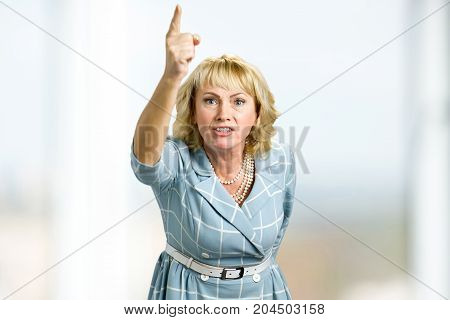 Frustrarted woman raised hand up. Furious mature woman arguing showing hand with index finger isolated.