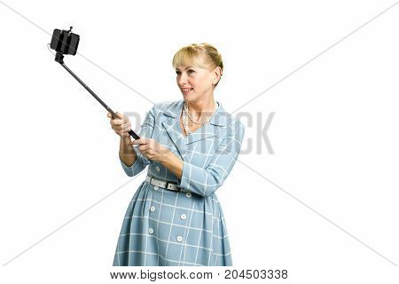 Mature woman using selfie stick. Beautiful smiling white-skin lady taking selfie isolated on white background.