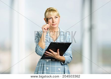 Thoughtful mature woman with clipboard. Thinking white-skin woman holding black clipboard and pen, blurred background.