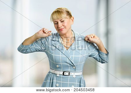 Stretching drowsy mature woman. Standing beautiful white-skin woman in dress, yawning and stretching close up.