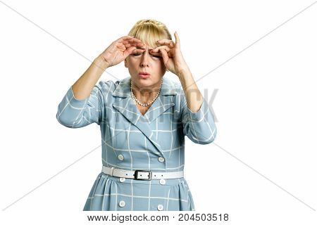 Drowsy mature woman in dress. Sleepy tired white-skin woman rubbing her eyes by hands isolated on white background.