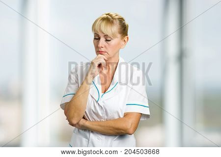 Confident thinking mature nurse. Portrait of thoughtful mature medical doctor holding chin on hand and thinking on blurred background.