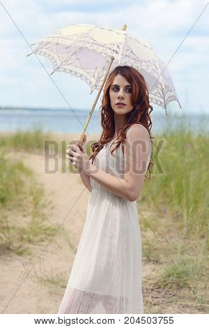 redhead woman with parasol on beach trail