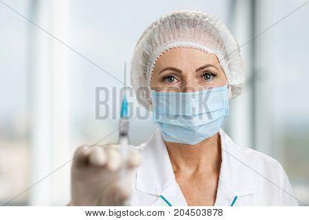 Professional nurse holding syringe with injection. Close up of syringe in female doctor hand on blurred background.