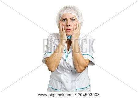 Beautiful female doctor looking shocked. Medical middle aged female doctor shocked and surprised. Woman medical professional reacting with negative shock on white background.