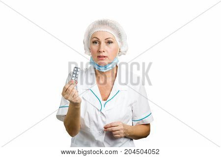 Attractive doctor holding blister of pills. Portrait of middle aged female doctor in white uniform giving medicine on white background.