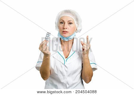 Female mature doctor prescribing pills. Mature female doctor in a white lab coat giving advice with her index finger pointing up, white background.