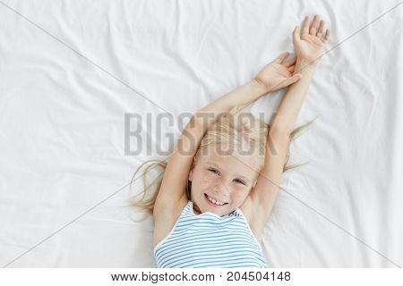 Happy Lovely Blond Little Female Child Relaxing In Bed, Lying On White Bedcloth And Stretching, Enjo