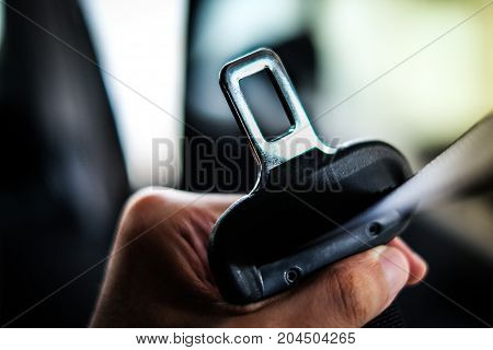 Hand of driver holding seat belt (safety belt) lock in car before driving - safety & secure concept.