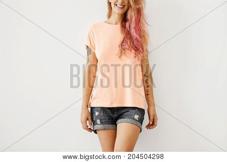 Cropped Studio Portrait Of Smiling Joyful Young Woman With Long Pinkish Hair And Stylish Tattoos On