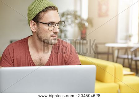 Portrait Of Talented Male Journalist Works On Article, Types Information At Laptop Computer, Wears S