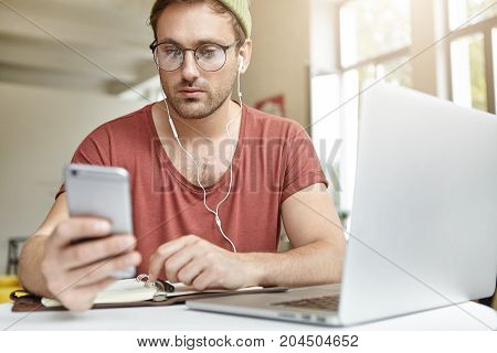 Young Bearded Guy Wears Big Spectacles, Checkes Newsfeed On Social Media, Listens To Songs On Mobile