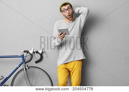 Astonished Male Racing Cyclist Wearing Fashionable Clothes, Looking At Tablet With Great Surprisment