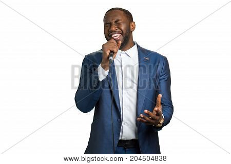 Afroamerican singer perfoming in studio. Professional vocalist perfoming. Black man is singing on white background.
