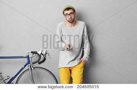 Studio Shot Of Puzzled Young Unshaven Male Hipster In Eyeglasses And Hat Having Confused And Clueles