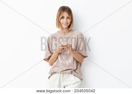 Waist Up Portrait Of Attractive Young Female Adult Wears Oversized T-shirt, Looks With Delightful Ex