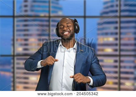 Happy dancing businessman on skyscraper background. Afro american positive manager listening music with headphones. Cheerful executive dancing on evening city background.