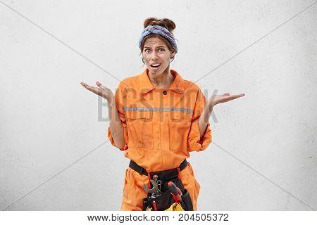 Studio Portrait Of Attractive Young European Woman Electrician In Orange Uniform, Shrugging Her Shou