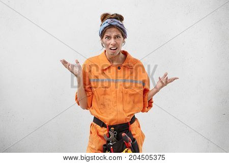 What Are You Talking About? Startled Confused Young Caucasian Female Maintenance Worker With Belt Ki