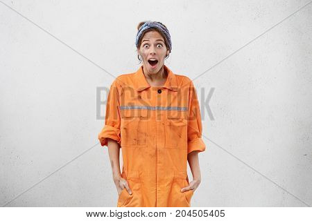 Portrait Of Emotional Young Female Technician In Orange Overalls Looking At Camera In Astonishment A