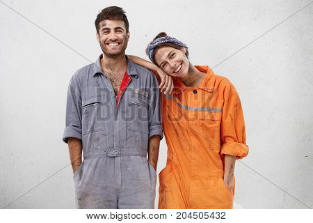 People, Manual Work And Team Work Concept. Smiling Joyful Female And Male Professional Workers, Bein