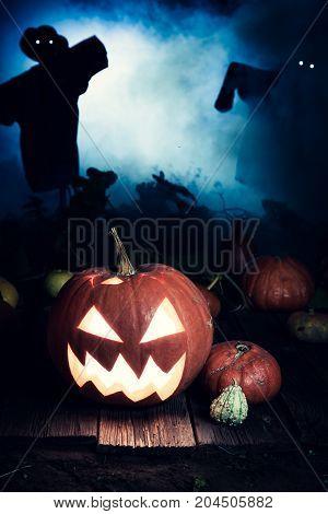 Orange Halloween Pumpkin With Blue Mist And Scarecrows