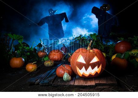 Orange Pumpkin With Blue Mist And Scarecrows For Halloween
