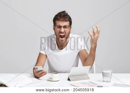 Picture Of Annoyed Bearded Male Wearing Glasses And Casual White T-shirt Sitting At His Workplace Ho