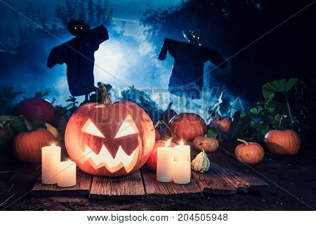 Scary Halloween Pumpkin With Scarecrows On The Field