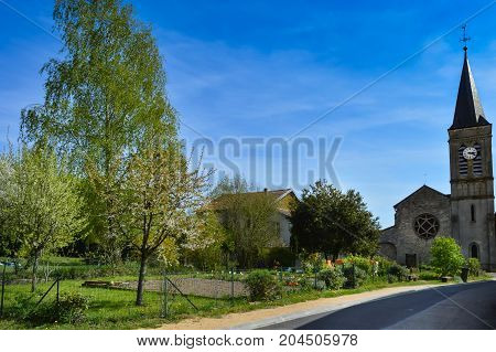 Small garden and old church in a small village near lake madine in the department of meuse in France