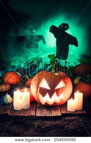 Scary Pumpkin On Dark Field With Scarecrows For Halloween