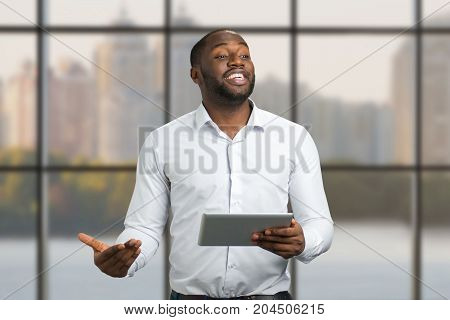 Cheerful businessman on city background. Joyful businessman using pc tablet, speaking and gesticulating. Enthusiastic presentation about successful achievement of young manager.