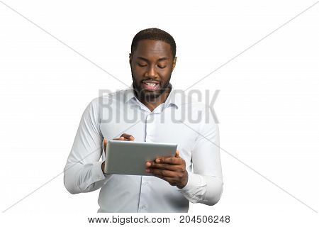 Black businessman using computer tablet. Successful company director reading important information on touch screen computer.